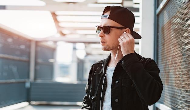 Ragazzo alla moda alla moda in un berretto nero e occhiali da sole con uno smartphone e cuffie sul tavolo di un tramonto urbano urbano.