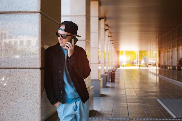Occhiali da sole alla moda alla moda con cappuccio nero da ragazzo con cuffie per smartphone urbano urbano tramonto