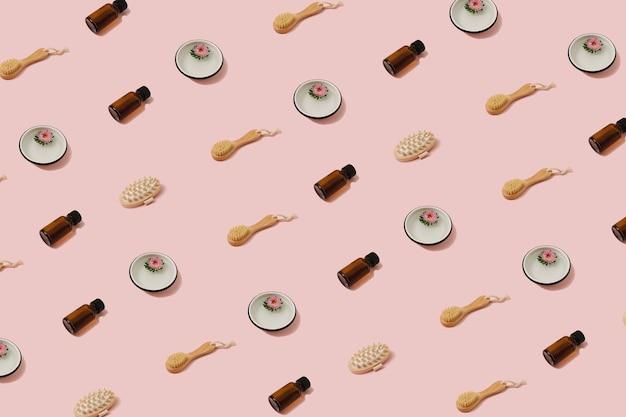 Modello di bellezza alla moda alla luce del sole realizzato con vari pennelli cosmetici, bottiglie e fiori su sfondo rosa pastello vibrante. concetto di cura di sé e benessere ecologico.