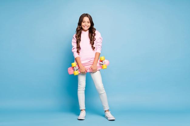 Adolescente alla moda in posa contro il muro blu