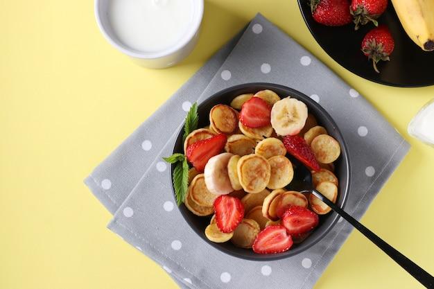 Alla moda minuscole frittelle per colazione con fragole e banana in ciotola scura su sfondo giallo e tazza di latte, vista dall'alto, primo piano
