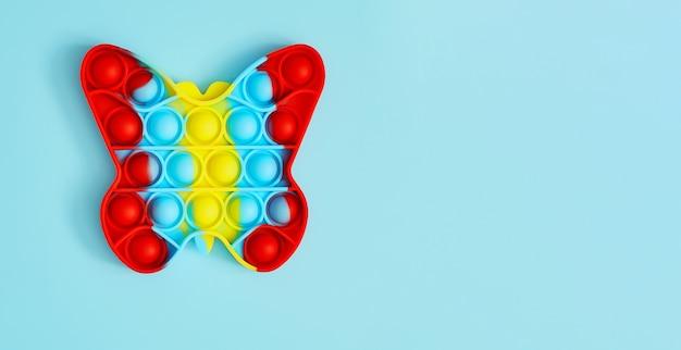 Giocattolo alla moda anti stress. bambino anonimo con gioco poppit colorato. vista dall'alto del nuovo giocattolo sensoriale
