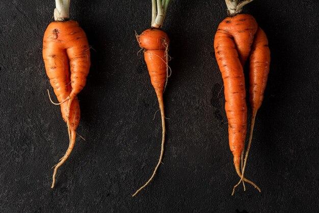 Alla moda brutte carote organiche dal letto del giardino di casa su sfondo nero. vista dall'alto