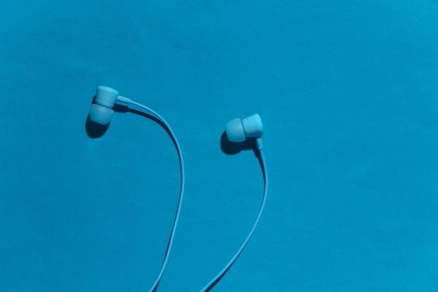 Auricolari cablati alla moda su uno sfondo blu con ombra. vista dall'alto
