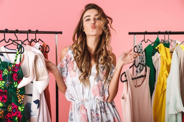 Donna alla moda in abito in piedi vicino al guardaroba con vestiti e scegliendo cosa indossare isolato sul rosa
