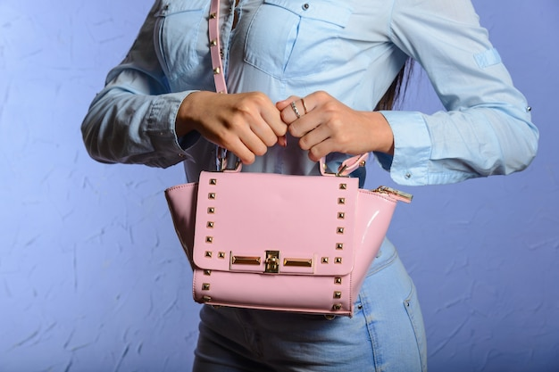 Donna alla moda in jeans e camicia di jeans con borsetta rosa
