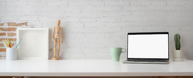 Area di lavoro alla moda con laptop, tazza di caffè, decorazioni e spazio di copia
