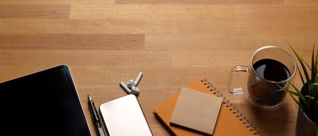 Tavolo da lavoro alla moda con copia spazio, smartphone, tablet, tazza di caffè e articoli di cancelleria
