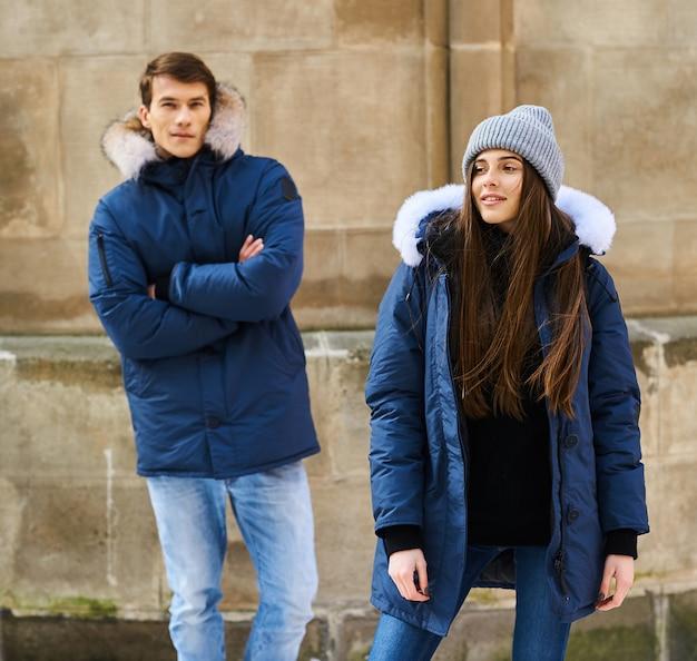 Una giovane coppia alla moda cammina in città a christmastime