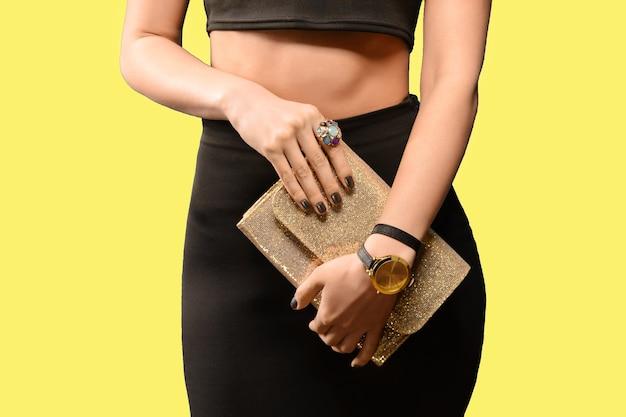 Ragazza d'avanguardia in gonna nera che tiene giallo borsa in pelle dorata