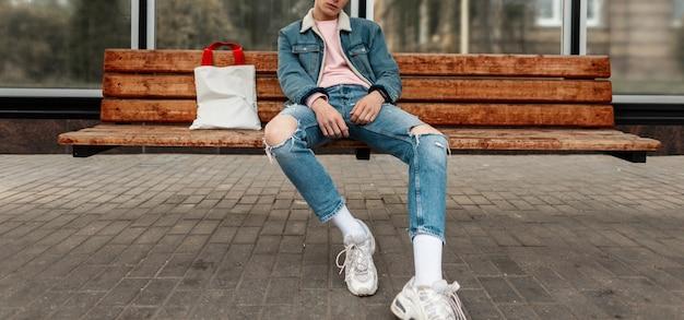Il giovane alla moda in giacca di jeans alla moda giovanile in jeans vintage casual con shopper in tessuto si siede su una panca di legno alla fermata dell'edificio pubblico in città. bel ragazzo in abiti alla moda per strada.