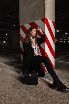 Giovane donna alla moda in elegante cappotto nero con sciarpa di seta elegante in stivali con borsa in pelle si siede sull'asfalto nel parcheggio vicino al pilastro in linee rosso-bianche. resti attraenti del modello di moda della ragazza.