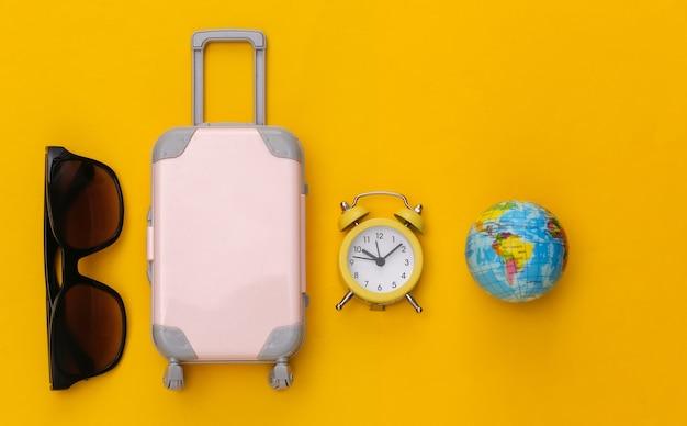 Trevel piatto disteso. mini bagaglio e sveglia, occhiali da sole e globo su sfondo giallo.