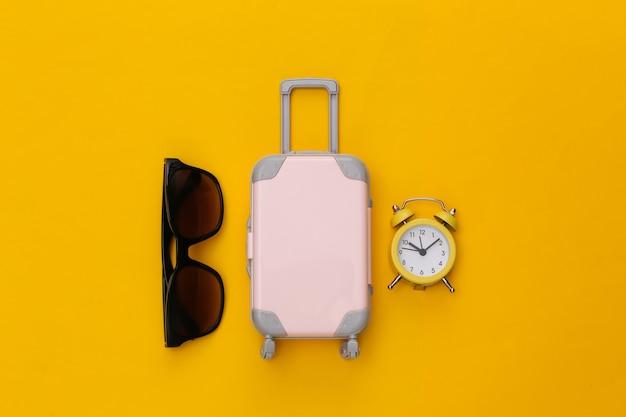 Trevel piatto disteso. mini bagaglio e sveglia, occhiali da sole su sfondo giallo.