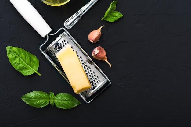 Pezzo triangolare di parmigiano su una grattugia, aglio, basilico verde. ingredienti alimentari per fare la pasta, spaghetti, bruschette, pizza, fettuccine, salsa al pesto .vista dall'alto, copia spazio, sfondo di cemento nero