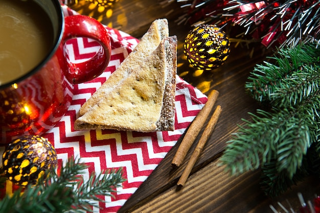 Biscotti triangolari con zucchero a velo e cannella su un tovagliolo con un motivo a zig-zag