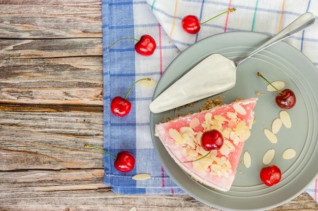 Fetta triangolare di dessert con ciliegie in un piatto grigio vista dall'alto su un tovagliolo