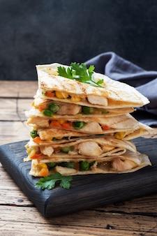 Fette triangolari di quesadilla messicana con salsa.