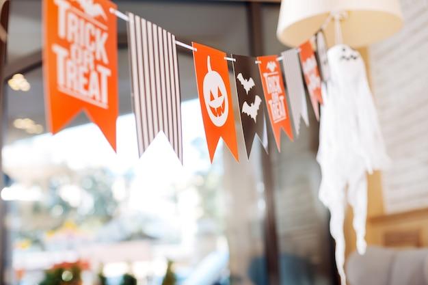 Dolcetto o scherzetto. belle decorazioni luminose con segno dolcetto o scherzetto che giace nella spaziosa sala eventi luminosa per la festa di halloween