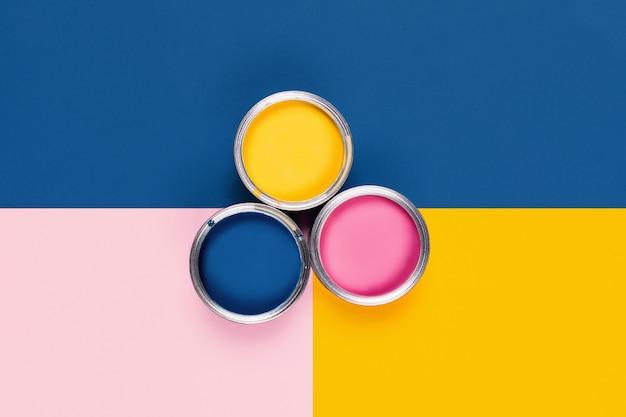 Tavolo tricolore con barattoli di vernice colorata.