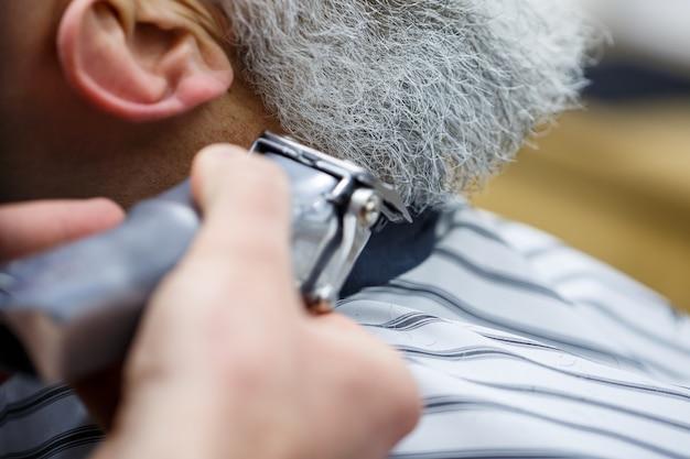 Tagliare la barba nel salone di un barbiere a un uomo