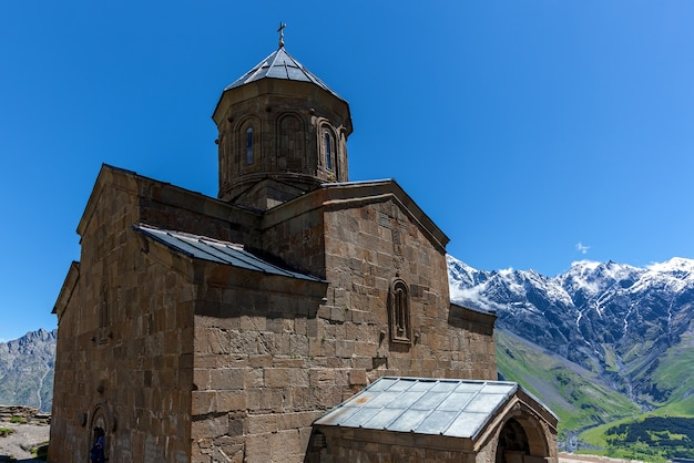 Chiesa della trinità sulla montagna sullo sfondo delle rocce nel villaggio di gergeti sull'autostrada militare georgiana