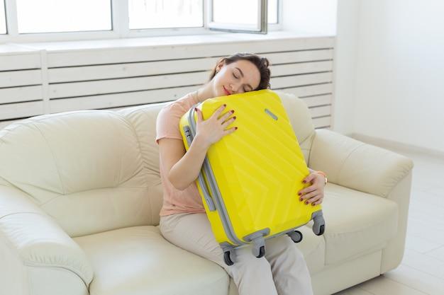 Concetto di viaggio, viaggi e vacanze - la donna è stanca di raccogliere cose per il viaggio