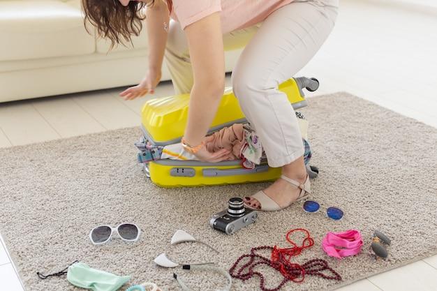 Concetto di viaggio, viaggio e vacanze - donna che cerca di chiudere la valigia.