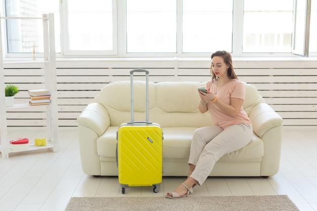 Concetto di viaggio, viaggio e vacanza: la donna con la valigia gialla sta aspettando il taxi.