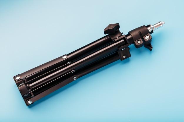 Treppiede su sfondo blu per una foto-videocamera e flash su sfondo blu.