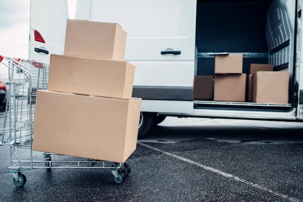 Carrello con scatole di cartone contro furgone postale. attività di distribuzione. consegna del carico. contenitori vuoti e trasparenti. logistica e servizio postale