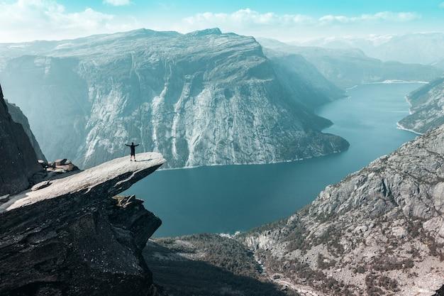 Trolltunga in norvegia con un uomo che ha aperto le braccia
