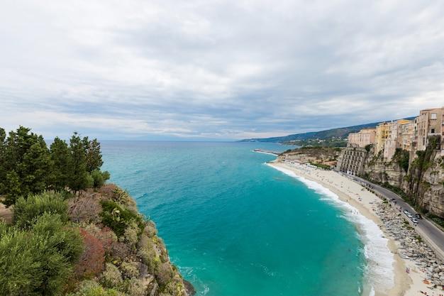 Città di tropea e costa della spiaggia del mar tirreno con acque turchesi, edifici colorati in cima a grandi rocce alte