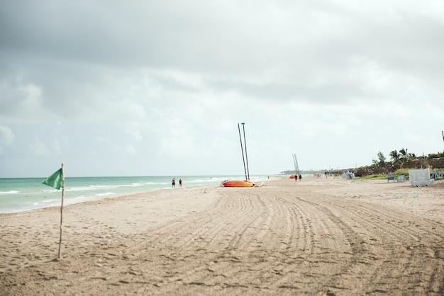 Vista incredibile della spiaggia tropicale spiaggia di sabbia bianca e chiara in una giornata estiva onde di mare blu si infrangono sulla spiaggia soleggiata paesaggio della spiaggia di palme di cuba cuba