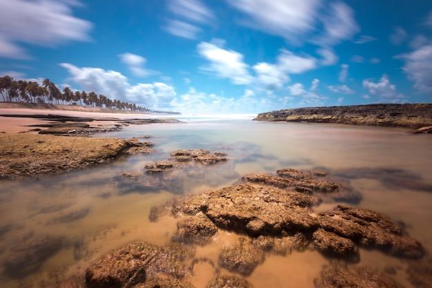 Paesaggio della spiaggia tropicale con palme da cocco e rocce a lunga esposizione.