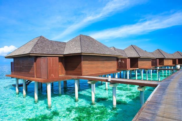 Spiaggia tropicale alle maldive con poche palme e laguna blu