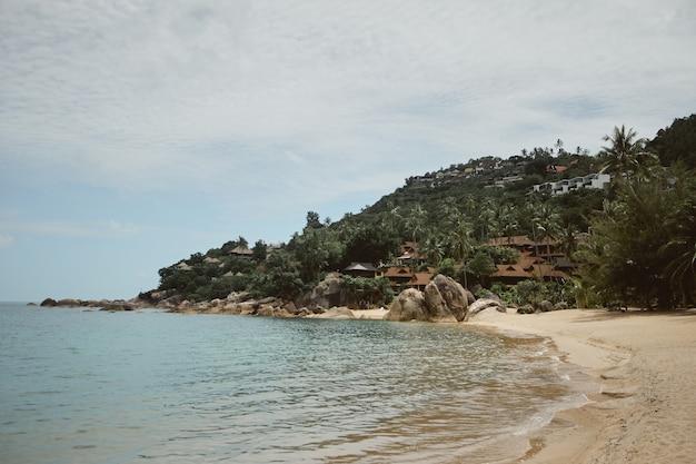 Spiaggia tropicale con piccole case sulla spiaggia e resort tra le palme sulla collina