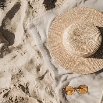 Bellissima spiaggia tropicale con sabbia bianca, gradini, coperta neutra con cappello di paglia e occhiali da sole