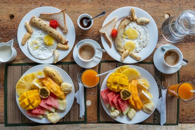 Colazione tropicale a base di frutta, caffè e uova strapazzate e pancake alla banana per due sulla spiaggia vicino al mare nel ristorante dell'hotel, isola di zanzibar, tanzania, africa, primo piano. vista dall'alto, tavola apparecchiata.
