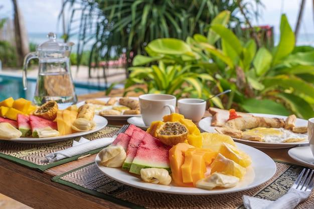Colazione tropicale di frutta, caffè e uova strapazzate e pancake alla banana per due sulla spiaggia vicino al mare nel ristorante dell'hotel, isola di zanzibar, tanzania, africa, primo piano