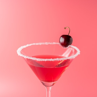 Cocktail tropicale con ciliegia sul rosa vivo