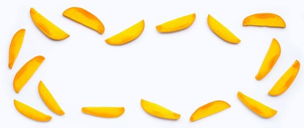 Frutta tropicale, cornice fatta di fette di mango su sfondo bianco.