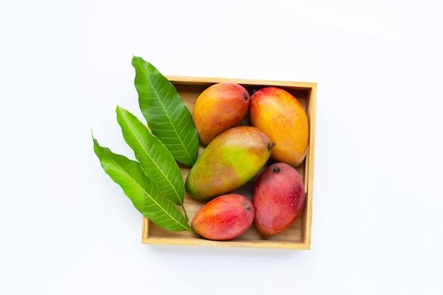 Frutta tropicale, mango fresco in scatola di legno su bianco isolata. vista dall'alto con spazio di copia