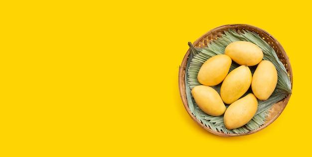 Frutta tropicale, mango in cesto di bambù su sfondo giallo.