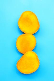 Frutta tropicale, mango su sfondo blu.