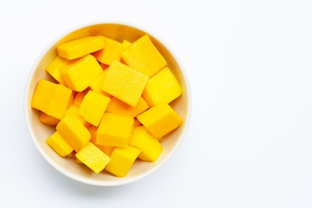 Frutta tropicale, fette del cubo del mango in ciotola bianca su bianco