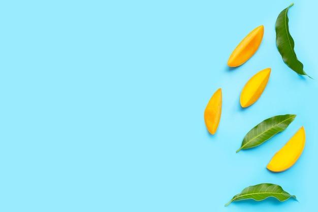 Frutta tropicale, fette di mango con foglie su sfondo blu.