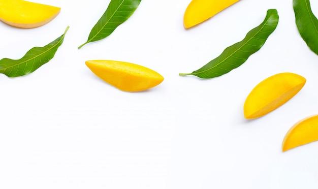 Frutta tropicale, fette del mango con sopra il fondo di bianco delle foglie.