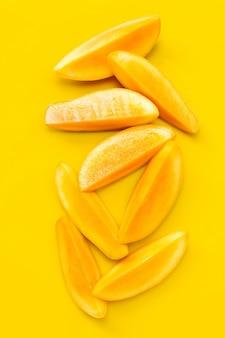 Frutta tropicale, fette di mango su giallo. vista dall'alto