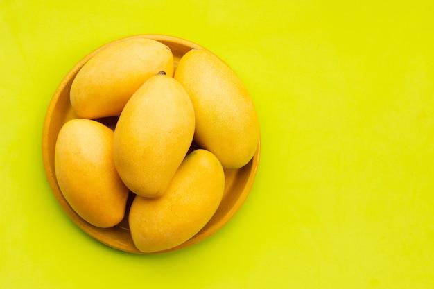 Frutta tropicale, mango nel piatto giallo su sfondo verde.